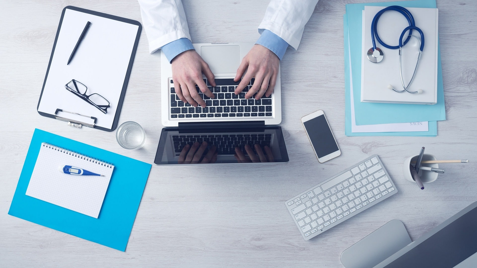 A doctor working with laptop, note, documents, thermometer, stethoscope