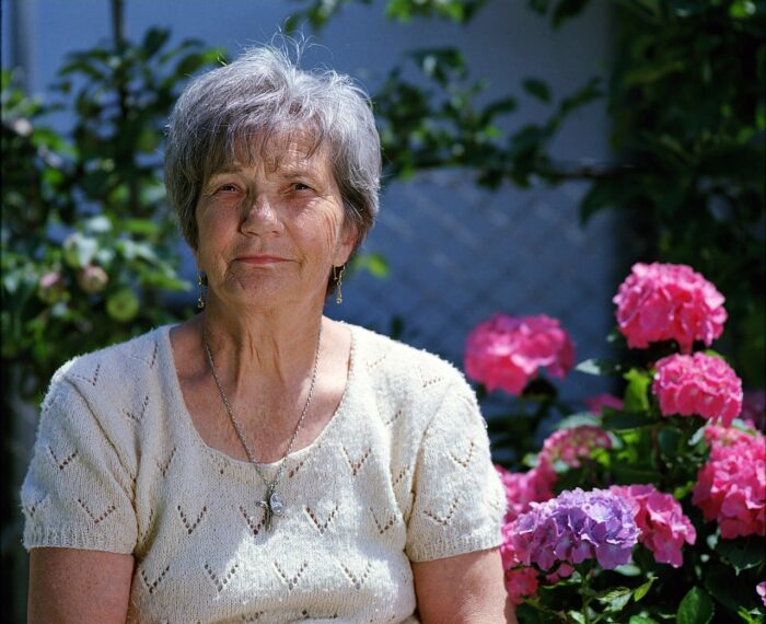 A senior woman sitting on the garden with flower