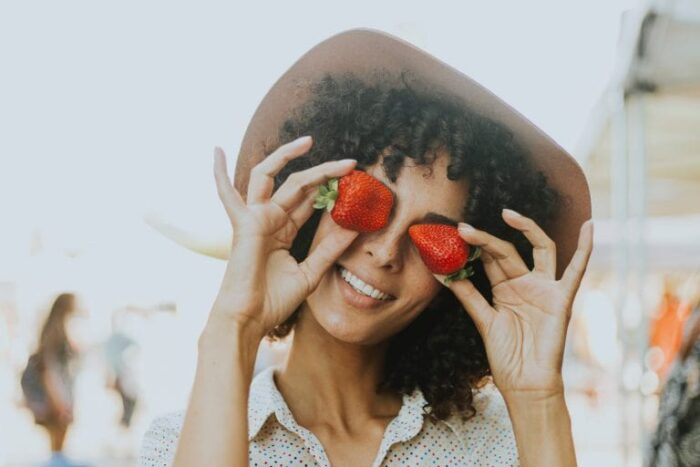 A woman holding 2 strawberry to cover her eyes.