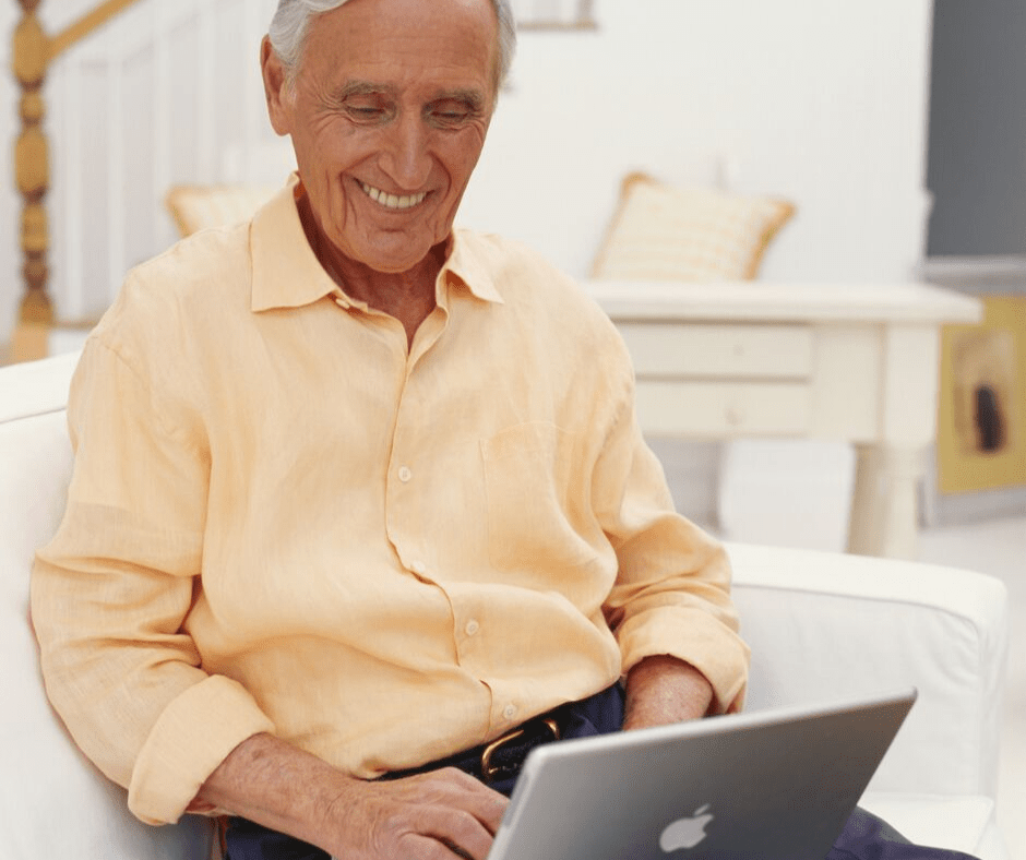 A smiling old man playing a Mac