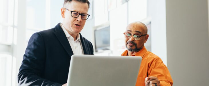 Two men looking something in laptop at workplace.