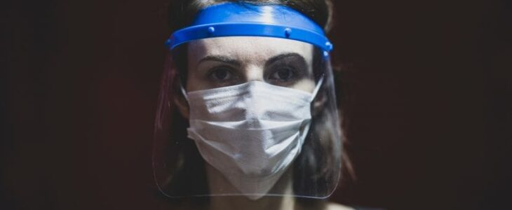 A woman wearing a face shield and surgical mask to protect her
