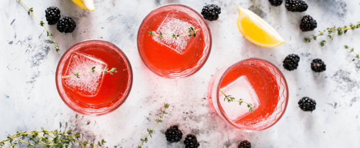 Three glasses of Mocktail with some lemon and blackberry.