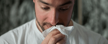 A man has allergies and holding a tissue