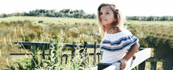 A little girl standing on meadow.