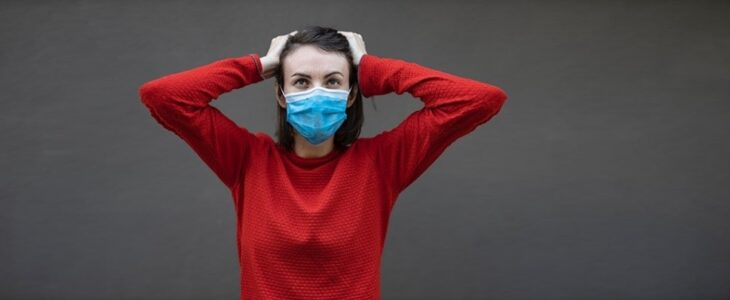 A woman wearing surgical mask and holding her head.